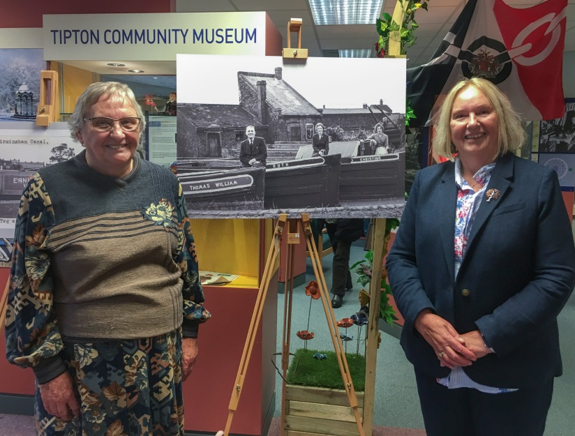 Ruth Collins and her sister Christine at in front of a photograph of themselves with their father Will King as part of the Will King Exhibition at Tipton Library, 2018